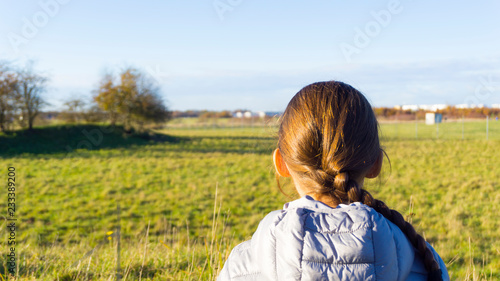 Lonely girl, teenager sitting on the grass in Park Canvas Print