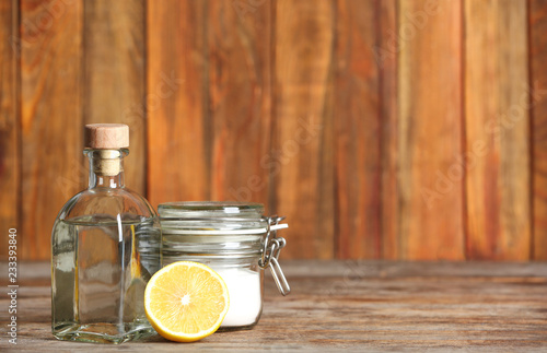 Composition with vinegar, lemon and baking soda on table. Space for text