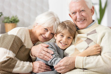 Loving Grandparents Cuddling On A Couch With Teenage Grandson