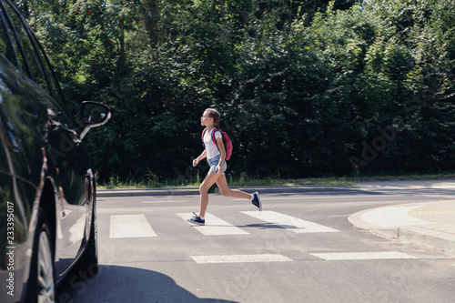 Tela Girl with backpack running through a pedestrian crossing next to car