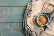 canvas print picture - Cup of hot winter drink and warm scarf on wooden background, top view with space for text. Cozy season