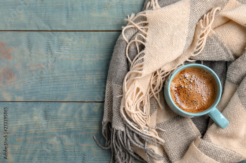 Cup of hot winter drink and warm scarf on wooden background, top view with space for text. Cozy season