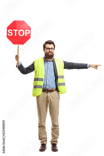 Man with a safety vest holding stop sign and pointing