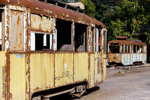 Old rusty destroyed trams outdoors at sunny day.