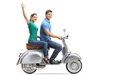 Young Male And Female Riding On A Vintage Motorbike, The Girl Waving