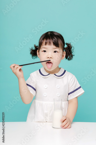 Fotografie, Tablou  Little pretty Asian girl laughing portrait with milk and bread, healthy and happy lifestyle