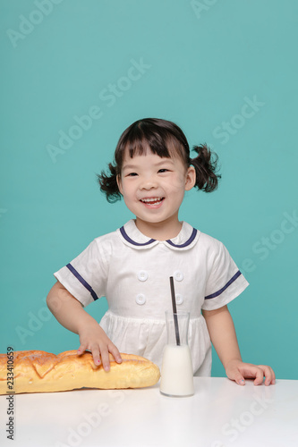 Little pretty Asian girl laughing portrait with milk and bread, healthy and happy lifestyle Wallpaper Mural