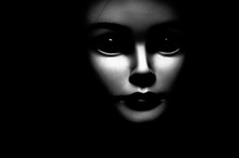 Close Up Of A Spooky Looking Black Eyed Child Looking Passed Viewer, Featuring Oversized Black Eyes, Pale Skin And Black Background.