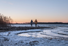 Loving Couple Holding Hands On The River At Sunset