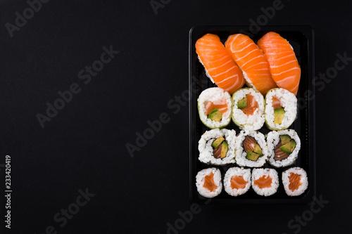 Fototapeta Japanese food: maki and nigiri sushi set on black background. Flat lay top-down composition. Copyspace obraz