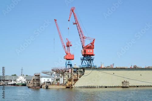 Poster Poort Fragment of ship dock with port cranes. City Svetlyj, Kaliningrad region