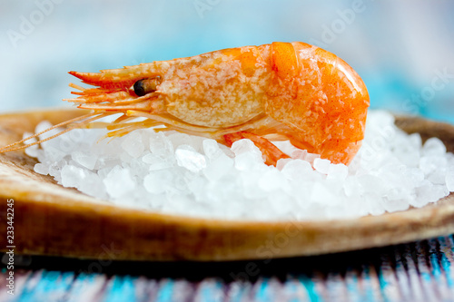 One shrimp in spoon with sea salt closeup