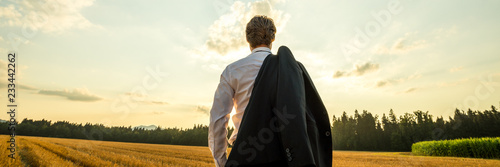 Fotografía  View from behind of a businessman standing in nature under evening sky