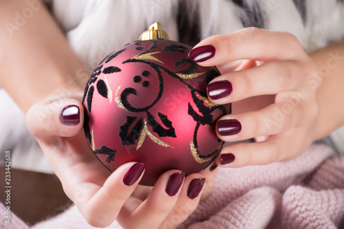 Obraz na plátně Girl with red wine color nails polish gel and holding Christmas ball decoration in hands