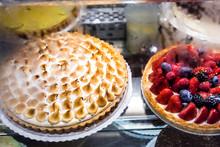 Many Cakes On Display In Bakery Shop Store With Lemon Cream Meringue, Blueberry Berry Strawberry Tart Decorations Whipped Cream, Egg Whites Caramelized