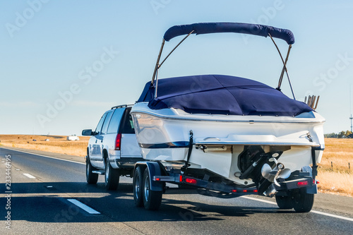 Fotografie, Obraz  Truck towing a  boat on the interstate, California