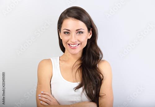 Fototapeta premium Frontowy widok piękna kobieta patrzeje z fałdowymi rękami w przypadkowej odzieży na bławym tle z pustą kopii przestrzenią z nagim makeup i zdrową połysk skórą