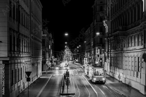 Tram stop Šilingrovo náměstí in Brno passing through public transport through night long street captured in black and white combination
