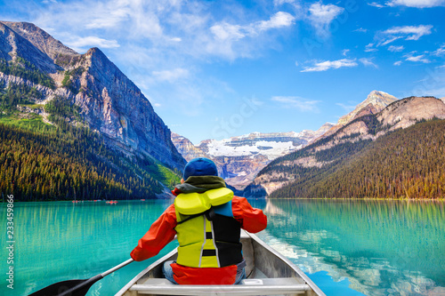 Foto auf Leinwand Kanada Boy Canoeing on Lake Louise in Banff National Park Canada
