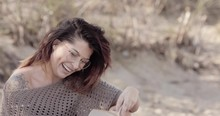 Beautiful Woman Reading On A Beach Notices The Camera Then Smiles And Laughs