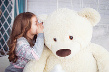 A Child Is Played With A Big Teddy Bear. A Girl Whispers In The Ear Of A Bear. A Fictional Friend.
