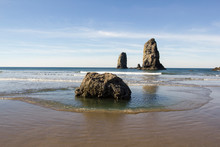 Sea Stacks In Cannon Beach On The Oregon Coast. High Tide Coming In Over The Rocky Shore And Forming Tide Pools.