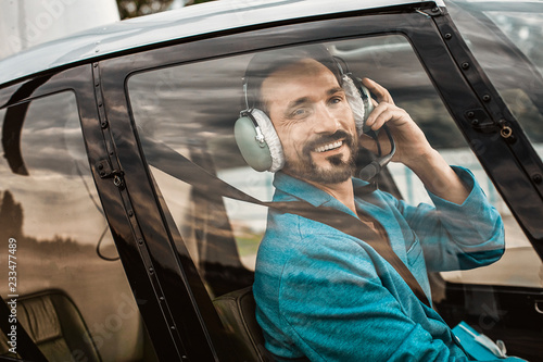 Positive handsome young man smiling while sitting in the helicopter cabin and touching his headphones