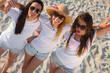 Tres chicas sexys de blanco en la playa sobre la arena riendo y haciendo selfies.
