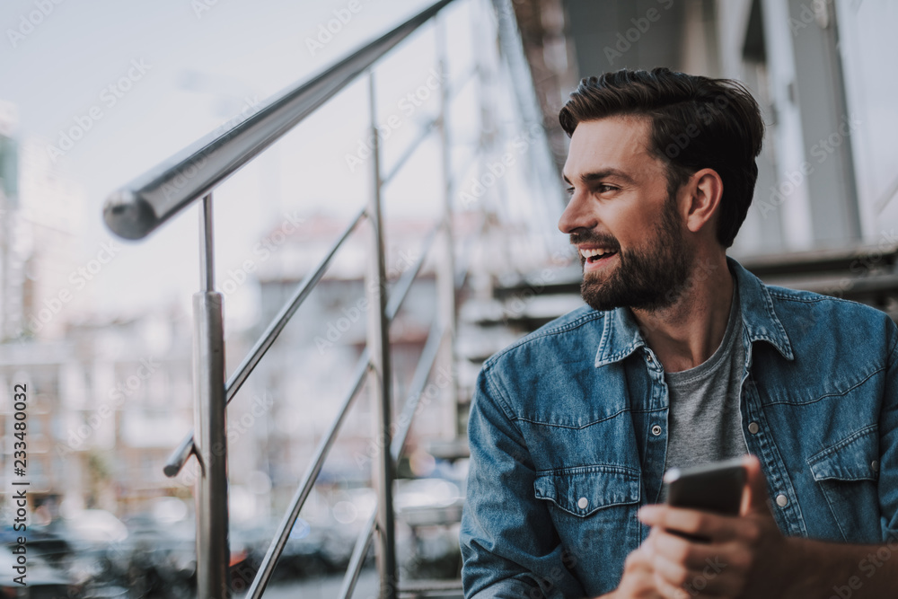 Fototapety, obrazy: Side view laughing unshaven man using modern phone outdoor. He locating on ladder while looking away