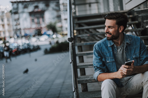 Fotografía  Side view laughing bearded male sitting on stairs while typing in mobile at street
