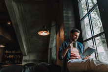 Portrait Of Cheerful Breaded Man Drinking Appetizing Mug Of Liquid While Reading Interesting Book Opposite Window Indoor. Glad Guy During Leisure Concept