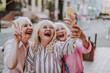 Leinwandbild Motiv Happy white-haired women making selfie. Laughing females dressing stylish clothes