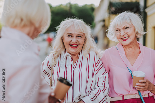 Valokuva  Waist up portrait of three smiling older ladies spending time together while dri