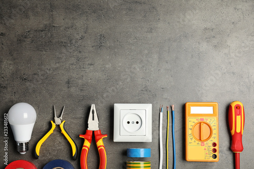 Cuadros en Lienzo  Electrician's tools and space for text on gray background, flat lay