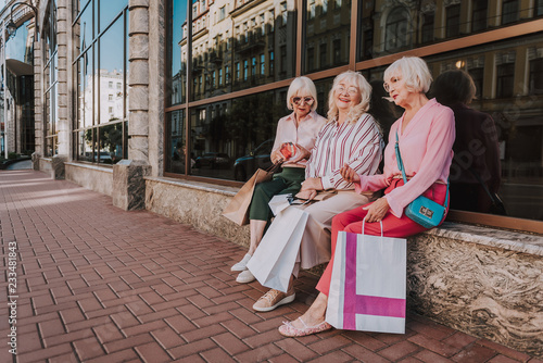 Photo  Full-length photo of three adult women discussing new purchases while holding shopping bags