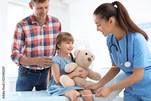 Children's doctor examining little girl near parent in hospital