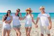 Cuatro amigos con camisetas blancas para anunciar una empresa en la playa.