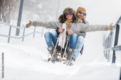 Obraz Young couple riding sled in snow - fototapety do salonu