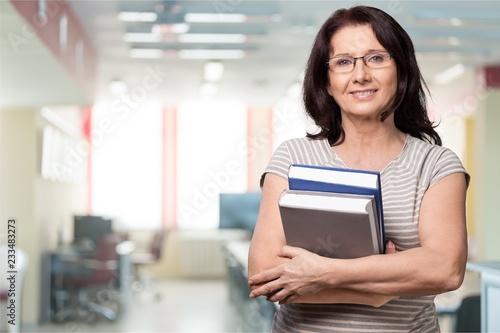 Mature woman teacher with books on background Fototapeta