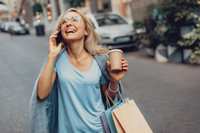 Waist Up Portrait Of Cheerful Middle-aged Lady In Glasses Talking On Cellphone On The Street. She Is Holding Cup Of Coffee And Shopping Bags