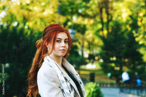 Fényképezés  Portrait of a young beautiful fashionable red-haired woman with long curly hair , posing on the streets of the European city