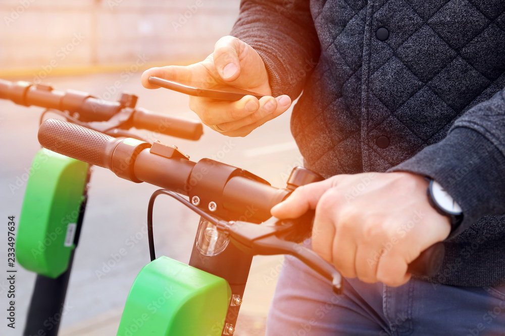 Fototapeta Close up image of a man on an electric scooter paying online