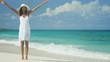Beautiful ethnic Hispanic girl wearing white dress on ocean beach
