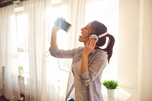 A girl in headphones sings a song against the window. - 233499292