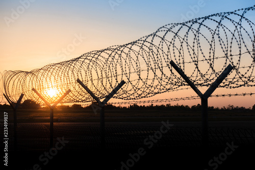 Silhouette of a barbed wire fence steel jail  with the sunset in the background Canvas Print