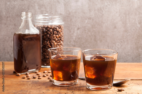 Photographie Cold brew coffee and coffee jar on the wooden table.