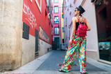 Fototapeta Uliczki - Woman with backpack in middle of narrow street