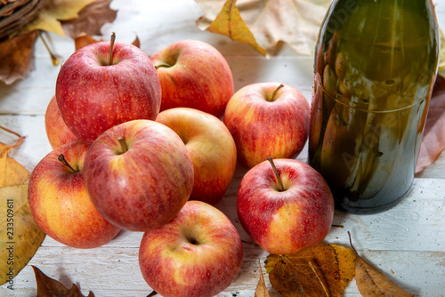 autumn leaves with bottle of cider and and apples Fototapeta