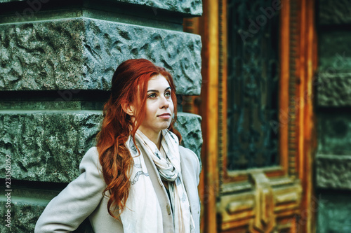 Fotografia  Portrait of a young beautiful fashionable red-haired woman with long curly hair , posing on the streets of the European city