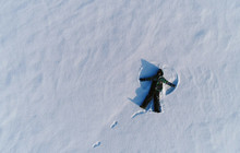 Boy Of 7 Years Makes Snow Angel In Snow Area. Aerial Foto.